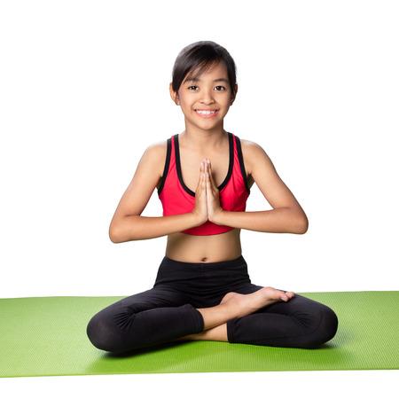 haciendo ejercicio: Pequeña muchacha asiática se sienta en una actitud de la meditación, aislado en blanco