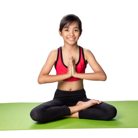 Little asian girl sits in a pose meditation, Isolated over white Archivio Fotografico