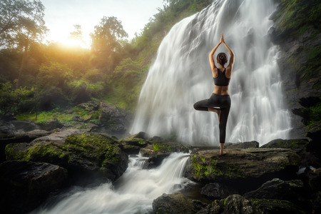 estilo de vida saludable: Mujer joven en una pose de yoga en la cascada