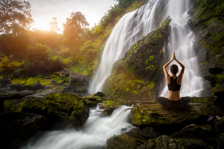 Young woman in a yoga pose at the waterfall