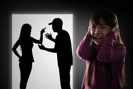 pelea: Llorando illtle muchacha asiática con sus padres que luchan en el fondo Foto de archivo