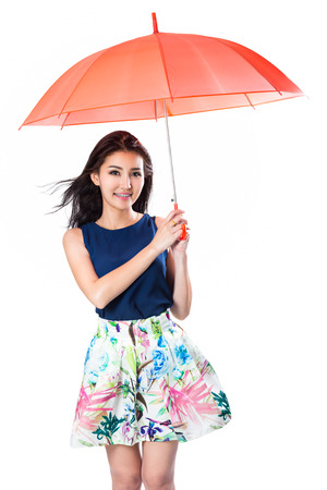 白で分離された風に傘を保持している若いアジア女性
