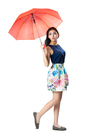 Young asian woman holding a umbrella in the wind, Isolated over white Foto de archivo