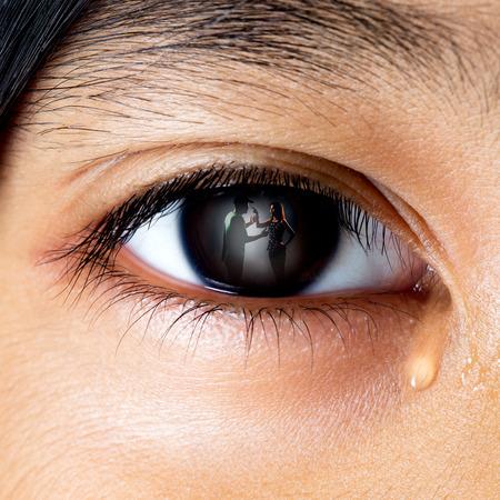 Close huilende kleine Aziatische meisje zoekt haar gevechten ouders in haar ogen