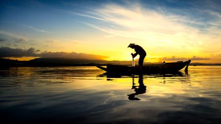 redes de pesca: Silueta del pescador asi�tico en el barco de la ma�ana Foto de archivo