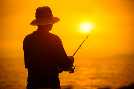 ocean fishing: Fisherman silhouette at sunset near the sea with a fishing rod