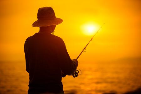 Silhouet van de visser bij zonsondergang in de buurt van de zee met een hengel Stockfoto
