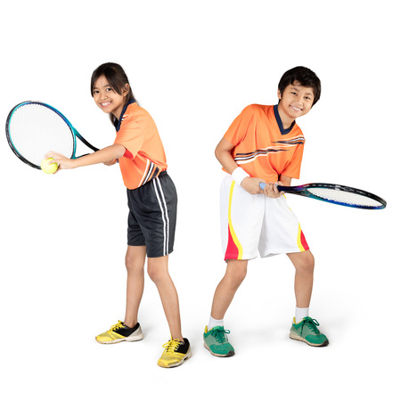 Young asian children playing tennis, Isolated over white Фото со стока