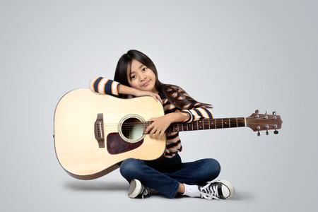 灰色の背景に分離されたアコースティック ギターと若いアジアの女の子 写真素材