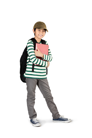 school children: Full length of young asian boy standing and holding books, Isolated over white