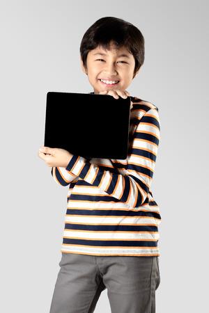 Giovane ragazzo con tavoletta digitale, isolato su sfondo grigio