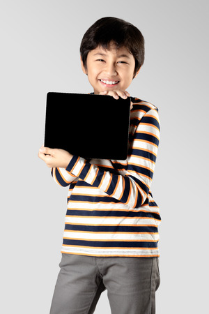 Young boy with digital tablet, Isolated on grey background