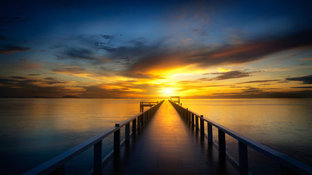 Bridge into the sea at sunset