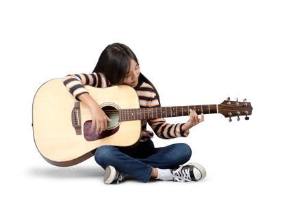 guitarra acustica: Muchacha asiática joven con una guitarra acústica, aislado sobre fondo gris