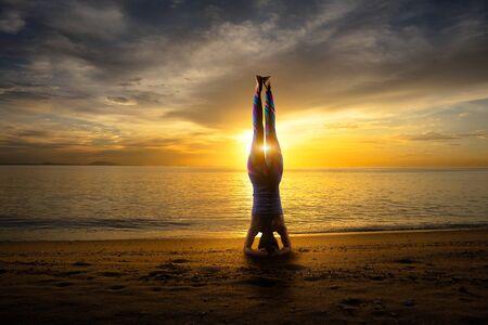 headstand: Sunset yoga woman Headstand on sea coast