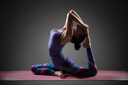 thai stretch: King of pigeon pose, Young asian woman doing yoga