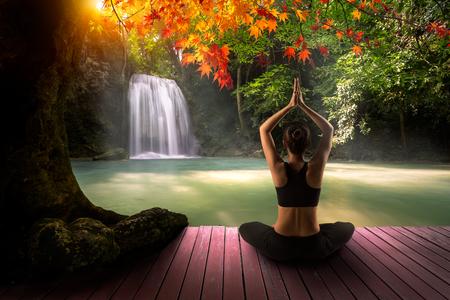 Giovane donna nella posa di yoga seduto vicino alla cascata, vista posteriore Archivio Fotografico - 47853152