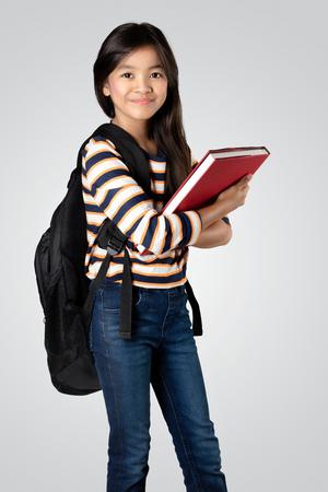 若いアジアの女の子立って押し書籍、灰色の背景に分離 写真素材