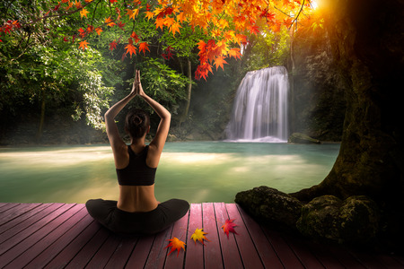 Young woman in yoga pose sitting near waterfall, Rear view