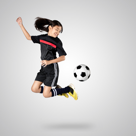 Jong Aziatisch meisje voetballer, die op een grijze achtergrond
