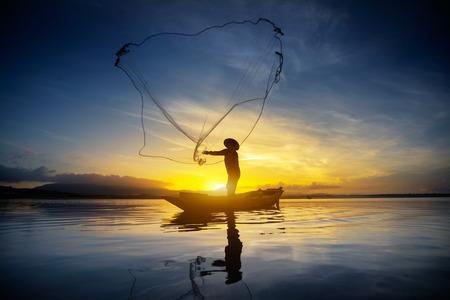 그물을 사용하여 어부의 실루엣 아침에 호수에서 물고기를 잡으려고