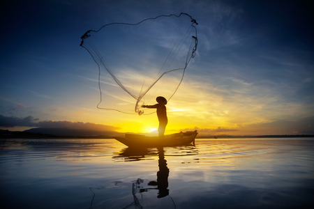 pescador: Silhouette of fishermen using nets to catch fish at the lake in the morning