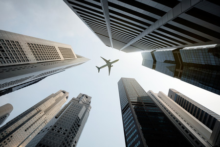 背の高いビルと頭上を飛ぶ飛行機