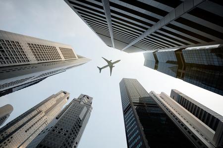 voyage avion: Grands bâtiments de la ville et une surcharge avion volant