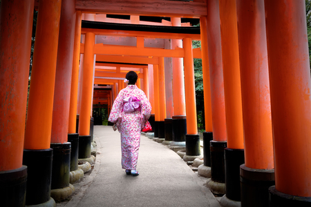 JAPON: Femme en costume traditionnel japonais marche sous portes tori au sanctuaire Fushimi-Inari, Kyoto