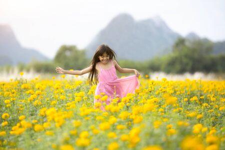 marigold: Happy little asian girl running on the marigold field