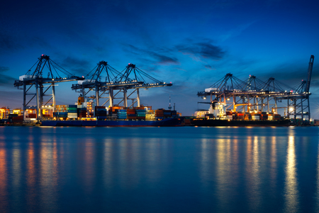 global logistics: Container Cargo freight ship with working crane bridge in shipyard at dusk for Logistic Import Export background