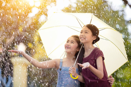 rainy: Pretty young asian girl in the rain with umbrella Stock Photo
