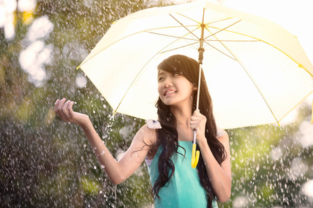 Pretty young asian girl in the rain with umbrella Banco de Imagens