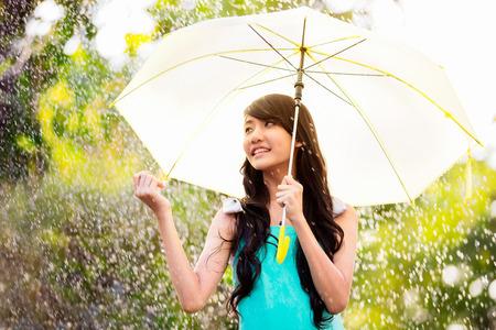 Hübsche junge asiatische Mädchen in der regen mit Sonnenschirm