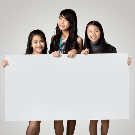 asian children: Group of kids showing blank placard board to write it on Stock Photo