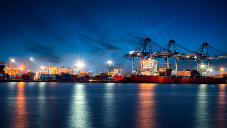 logistics: Container Cargo freight ship with working crane bridge in shipyard at dusk for Logistic Import Export background
