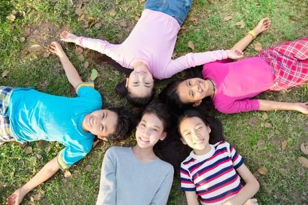 Lachende jonge jongens en meisjes liggen op groen gras
