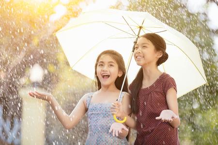 lluvia: Bastante joven muchacha asiática en la lluvia con paraguas