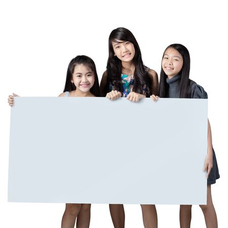 hold on: Group of kids showing blank placard board to write it on Stock Photo