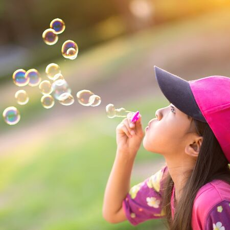 female child: Asian little girl is blowing a soap bubbles