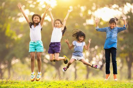 屋外の公園で一緒にジャンプ楽しい幸せなアジア家族