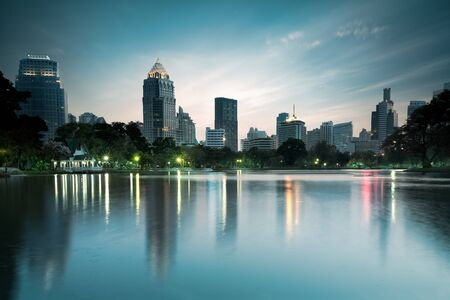 lumpini: Business district cityscape from a park with twilight time from lumpini park, Bangkok Thailand Stock Photo