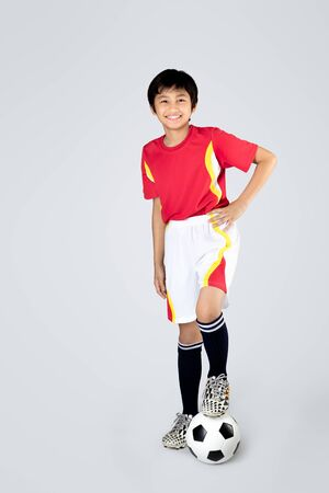 thai boy: Cute asian boy playing soccer, Isolated on grey background Stock Photo