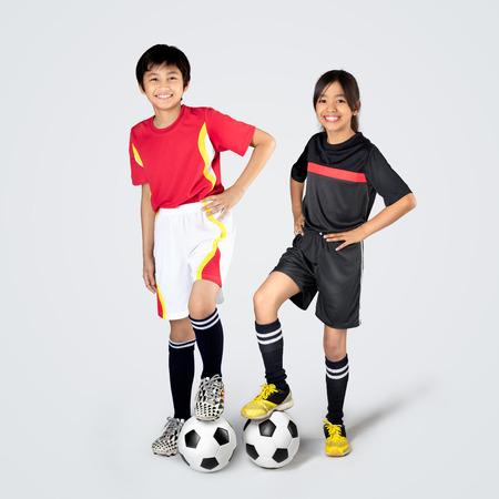 Jonge Aziatische kinderen voetballen, geïsoleerd op een grijze achtergrond