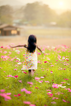 Little girl running in the garden flowers on a clear day Stockfoto