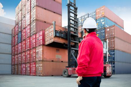 carretillas almacen: control de capataz de la caja de carga de contenedores desde el buque de carga por carretera