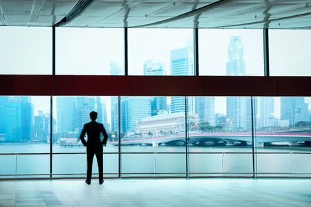 Businessman standing against room with large window looking on city photo