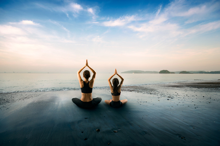 Mother and daughter doing yoga at beach