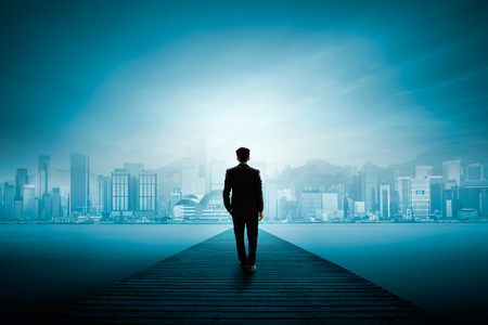 Busness man standing on wooden bridge and looks at the city