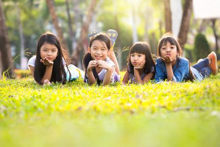 日光の下で緑の草を置く小さなアジアの女の子 写真素材